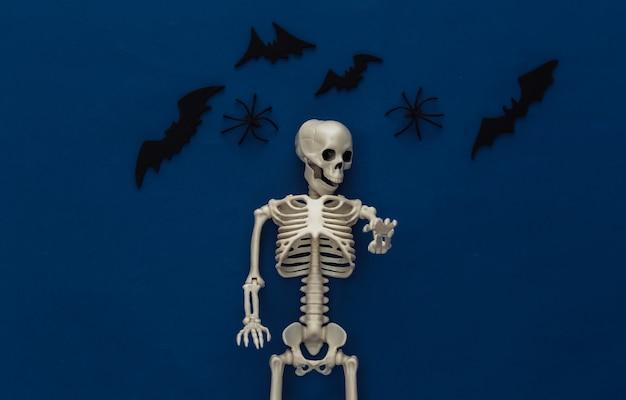 Halloween, decorações e conceito assustador. esqueleto e aranhas, morcegos pretos voam sobre o clássico azul escuro