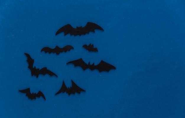 Halloween, decorações e conceito assustador. morcegos pretos voam sobre a noite azul escura