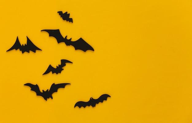 Halloween, decorações e conceito assustador. morcegos pretos voam sobre amarelo