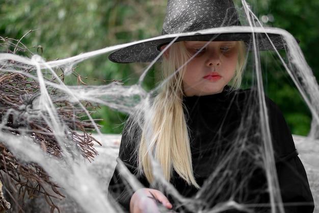 Halloween e crianças. menina de chapéu preto com aranhas e teias de aranha, retrato