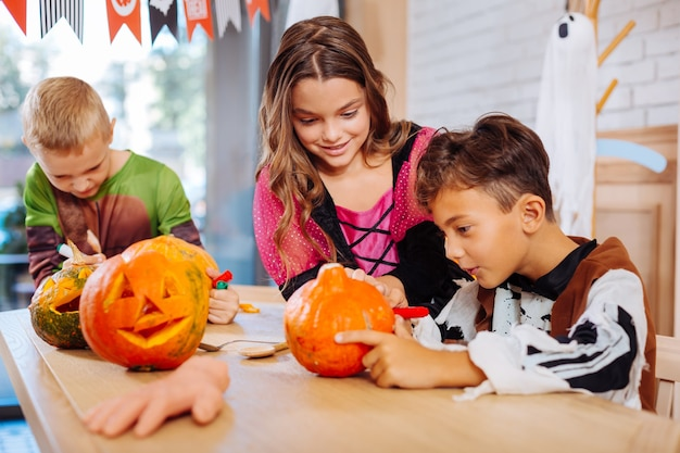 Halloween e família. três crianças animadas e fofas decorando abóboras enquanto se preparam para a festa familiar de halloween