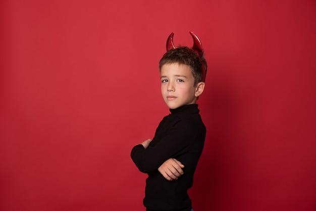 Halloween feliz criança rindo alto com chifres diabólicos contra um fundo vermelho de estúdio