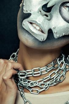 Halloween, feriados, estilo de vida, pessoas, beleza, conceito criativo - halloween e tema de maquiagem criativa: modelo de menina bonita com corpo preto com máscara de prata caveira pintada em fundo escuro no estúdio
