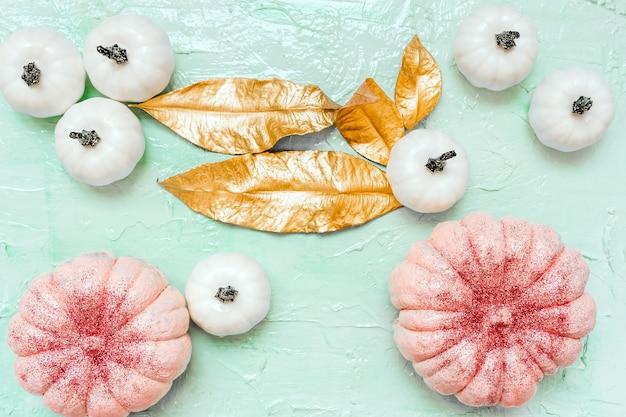 Halloween glitter rosa, abóboras brancas e folhas de ouro sobre fundo de hortelã