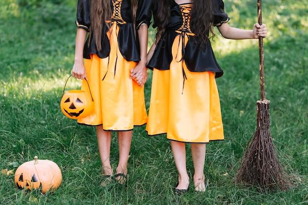 Halloween jovem vestida meninas com abóbora e vassoura na floresta