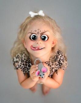 Halloween menina engraçada com olhos grandes e assustadores, sorriso com a língua e rato de brinquedo nas mãos dela. vista do topo.