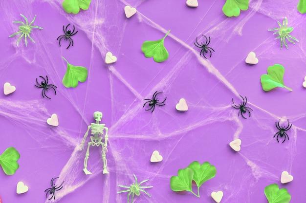Halloween plano plano com folhas de ginkgo verde neon, teia de aranha e aranhas pretas em papel roxo vibrante.