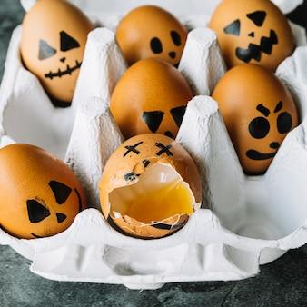 Halloween retratado ovos deitado na caixa com um quebrado