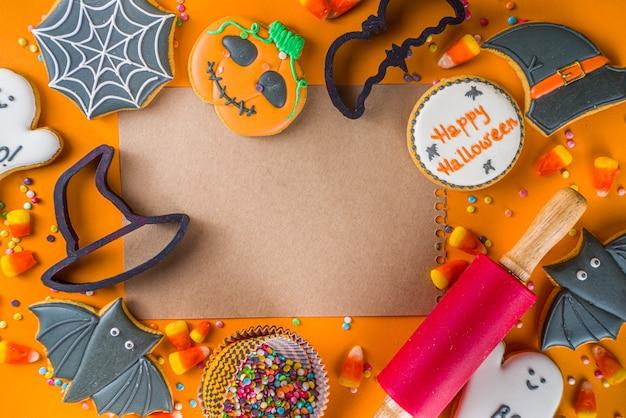 Halloween trata de fundo com biscoitos de gengibre açucarados e doces, conceito de doçura ou travessura vista superior cópia espaço, fundo moderno de cor laranja brilhante