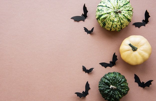 Halloween voando morcegos e abóboras em fundo marrom