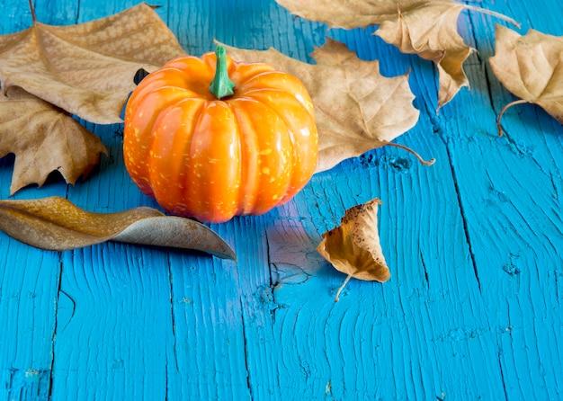 Hallowen de abóbora cercado por folhas secas de outono