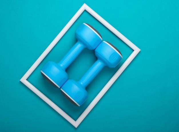 Haltere de plástico na superfície azul com moldura branca