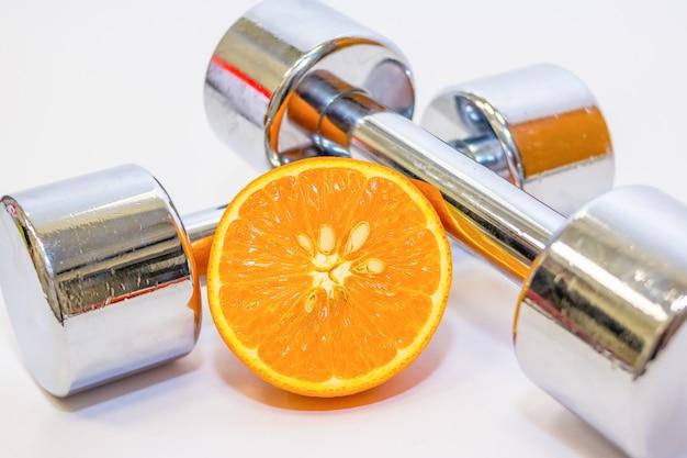 Haltere e laranja. suplementos de musculação esportiva. ginástica.