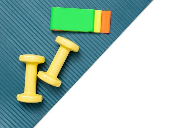 Halteres amarelos e um conjunto de elásticos multicoloridos de diferentes cores para fitness