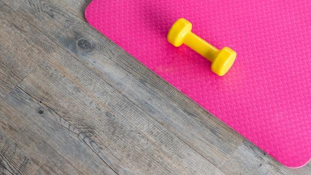 Halteres amarelos sobre um piso de borracha rosa vazio no piso de madeira