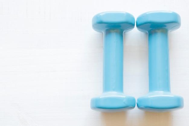 Halteres azuis claros para fitness pesando 1,5 kg sobre uma mesa de madeira branca