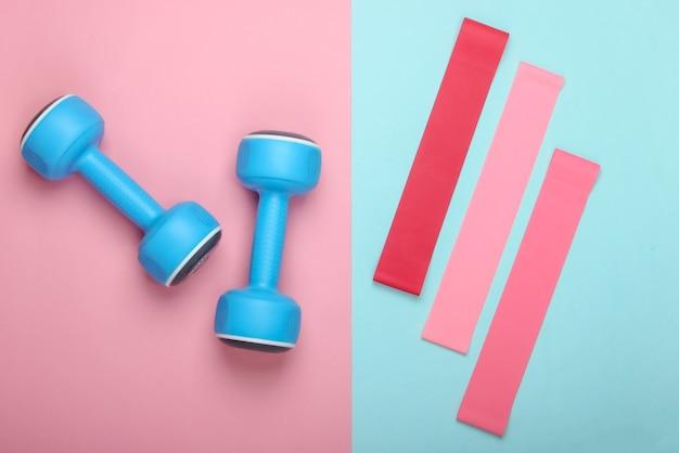 Halteres com elásticos de fitness em fundo rosa azul pastel. vista superior, configuração plana