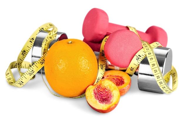 Halteres com fita métrica e frutas isoladas no fundo branco