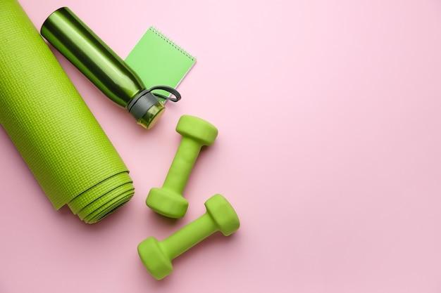 Halteres com notebook, tapete de ioga e garrafa de água na cor de fundo