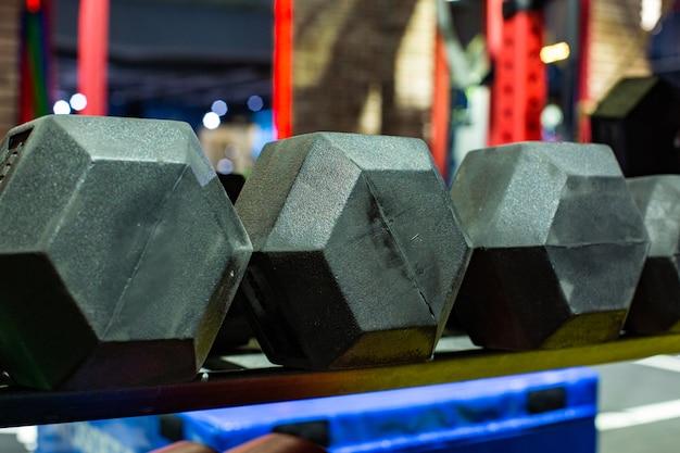 Halteres de borracha preta. conjunto de pesos pesados hexagonal usado para exercícios sérios de ginástica hardcore, treinamento para ajuste cruzado e rotinas de treino