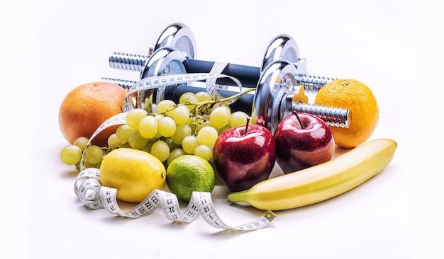 Halteres de cromo rodeados com frutas saudáveis, fita métrica em um fundo branco com sombras. dieta e exercício de estilo de vida saudável.