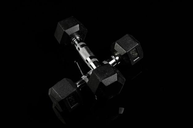 Halteres de esportes com alça de borracha preta sobre fundo preto isolado