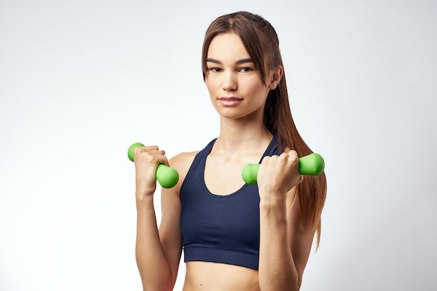Halteres de exercícios de fitness de mulher bonita nas mãos de uma luz forte de fundo