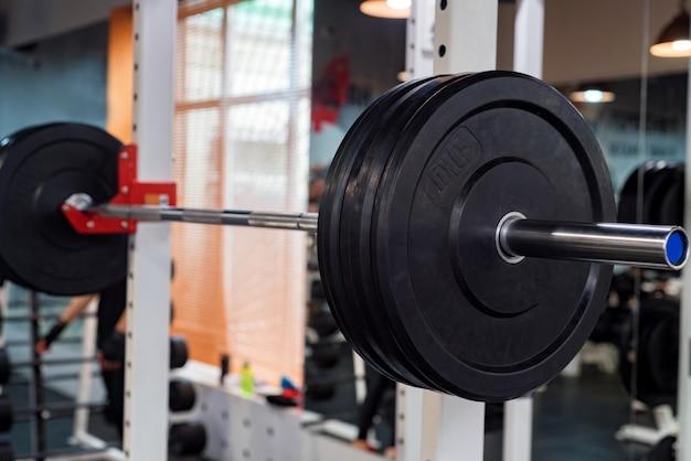 Halteres de fitness e placas de peso com barra em uma academia moderna