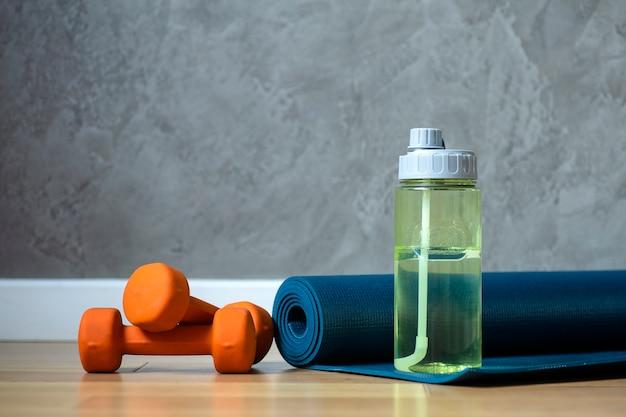 Halteres de fundo da sala de fitness e ioga e uma esteira no piso de madeira