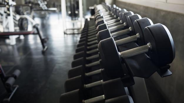 Halteres de metal na prateleira do rack para treinamento de força de fisiculturismo em academia de ginástica