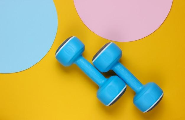Halteres de plástico em fundo amarelo com círculos azuis pastel rosa para espaço de cópia. vista do topo. conceito de esporte minimalista.