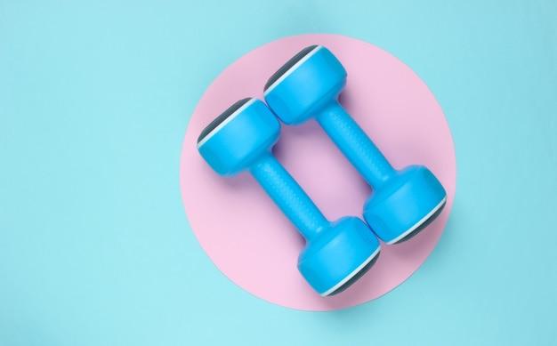 Halteres de plástico sobre fundo azul com círculo rosa pastel. vista do topo. conceito de esporte minimalista. vista do topo