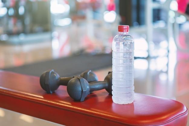 Halteres e água em um assoalho de borracha preta vazia no interior do ginásio esporte desfocado