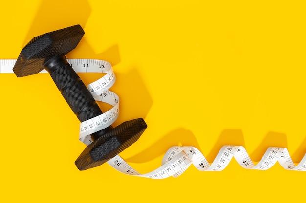 Halteres e fita métrica em fundo amarelo. conceito de exercício ou perda de peso. copie o espaço