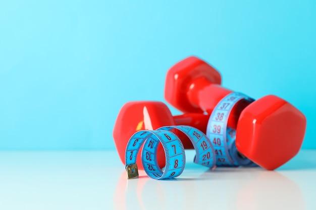 Halteres e fita métrica na mesa branca contra um fundo azul