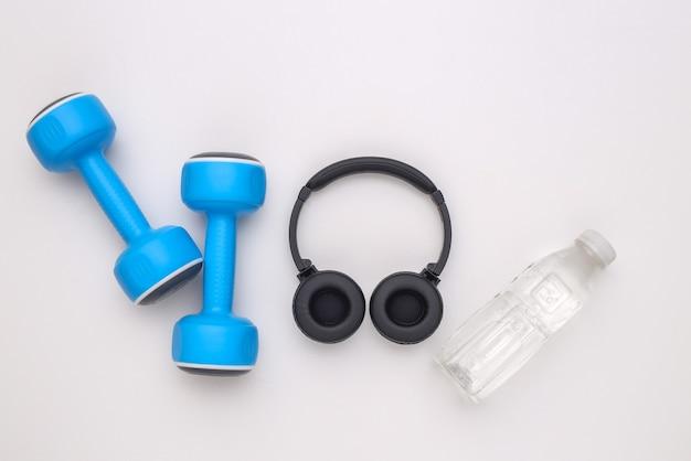 Halteres e fones de ouvido estéreo, garrafa de água no fundo branco. conceito de esporte e fitness. vista do topo
