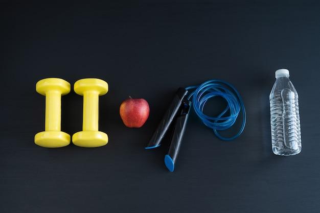 Halteres e pular corda em fundo preto para exercícios em casa. copie o espaço. Foto Premium