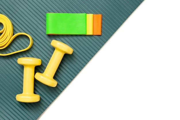 Halteres e um conjunto de elásticos multicoloridos de diferentes cores para a preparação física em um tapete esportivo