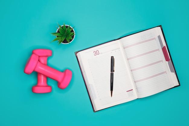 Halteres e um diário para registrar a atividade física da nutrição adequada
