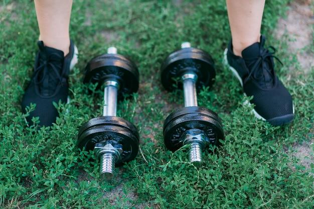 Halteres em fundo de grama verde e foots em tênis pretos