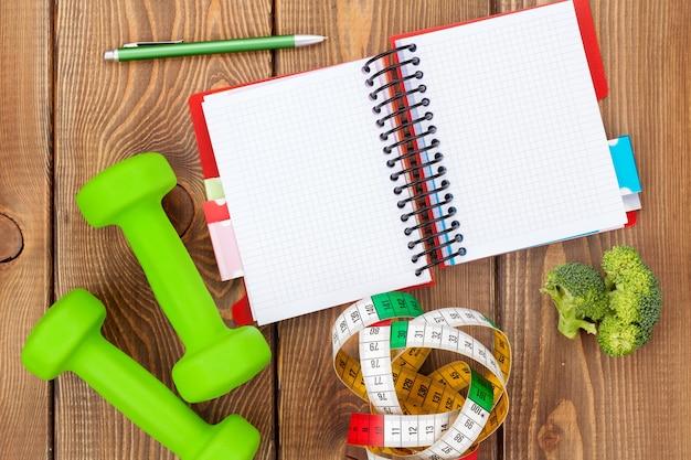 Halteres, fita métrica, alimentação saudável e bloco de notas para espaço de cópia. fitness e saúde. isolado em fundo branco