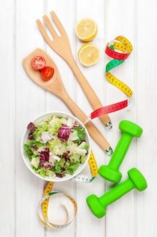 Halteres, fita métrica e alimentação saudável. fitness e saúde. vista de cima sobre a mesa de madeira