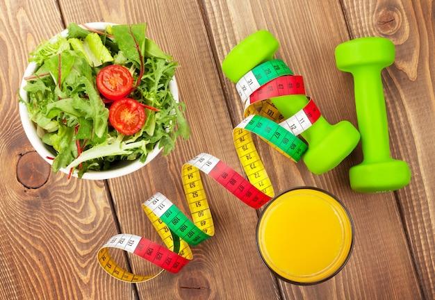 Halteres, fita métrica e comida saudável sobre a mesa de madeira. fitness e saúde. vista de cima