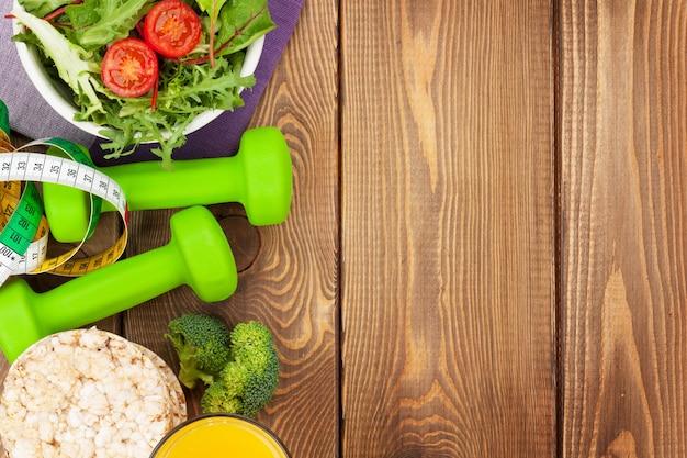 Halteres, fita métrica e comida saudável sobre uma mesa de madeira com espaço de cópia. fitness e saúde