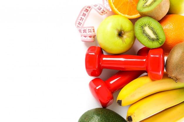 Halteres, fita métrica e frutas isoladas no branco