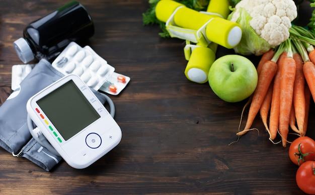 Halteres monitor de pressão arterial e frutas frescas com vegetais contra a mesa de madeira estilo de vida saudável e conceito de prevenção da hipertensão