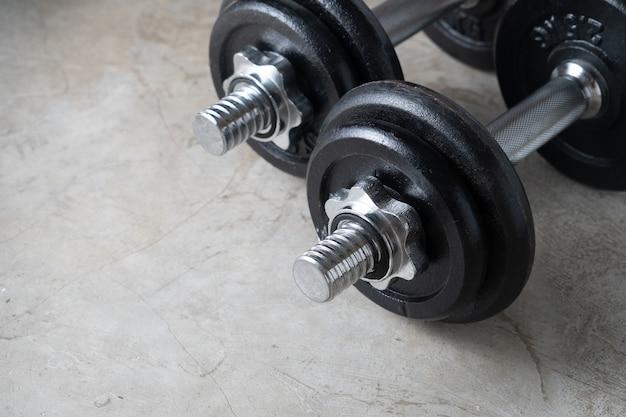 Halteres para exercício de construção muscular colocados no chão de cimento com copyspace. treino corporal no conceito de treinamento de ginástica. novos estilos de vida populares normais para musculação forte e saudável em casa