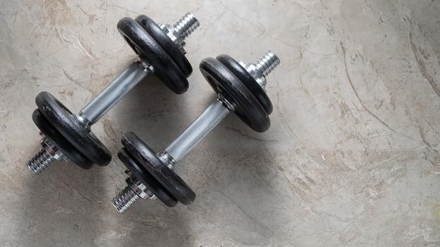 Halteres para exercícios de construção muscular colocados no chão de cimento