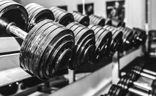 Halteres pesados deitado em bruto no ginásio. motivação do esporte de fitness. vida de estilo de vida saudável e feliz. exercícios com pesos de barras. foto em preto e branco.