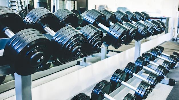 Halteres pesados deitado em bruto no ginásio. motivação do esporte de fitness. vida de estilo de vida saudável e feliz. exercícios com pesos de barras.
